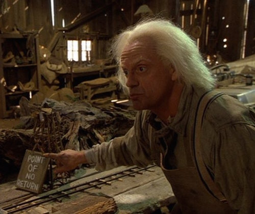 "Doc Brown pointing at a sign in a miniature model that says ""Point of no return"""